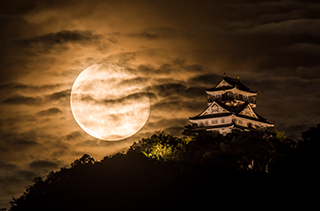 The rising moon behind Gifu Castle
