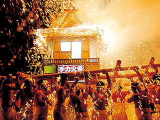 A portable shrine wildly swung by men under cascades of fireworks sparks.